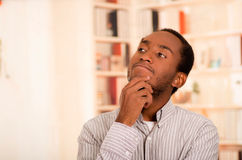 Man wearing casual clothes posing thoughtfully for camera, interacting using hands, white bookshelves background Stock Image