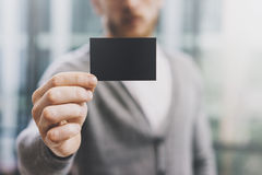 Man wearing casual shirt and showing blank black business card. Blurred abstract background. Horizontal mockup. Man wearing casual shirt and showing blank black Stock Photo