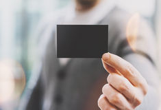 Man wearing casual shirt and showing blank black business card. Blurred background. Ready for private information. Horizontal Stock Photos