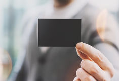 Man wearing casual shirt and showing blank black business card. Blurred background. Ready for private information. Horizontal mockup, film effect Royalty Free Stock Image