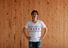 Man wearing Chicago flag color shirt and standing with akimbo on the wooden wall background. The city of Chicago is the most populous city in Illinois, United stock photo