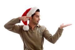 Man wearing christmas hat and indicating. Young man wearing christmas hat and indicating to his hand with white background Royalty Free Stock Images