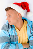 Man wearing christmas hat and listening to music. On an isolated white background Royalty Free Stock Image