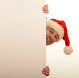 Man wearing Christmas hat peering out Stock Photography