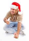 Man wearing christmas hat and showing thumbs up. Against white background Royalty Free Stock Images