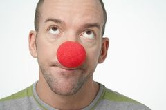 Man Wearing Clown Nose. Closeup of man wearing clown nose looking upwards isolated over white background Royalty Free Stock Image