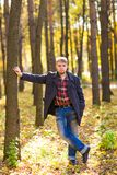 Man wearing a coat in the autumn park Stock Photos