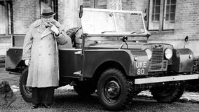 Man Wearing Coat Holding a Tobacco Standing Beside a Classic Car Stock Photo