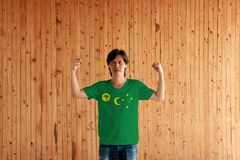 Man wearing Cocos Keeling Islands flag color of shirt and standing with raised both fist on the wooden wall background royalty free stock photography