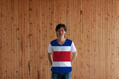Man wearing Costa Rica flag color of shirt and standing with crossed behind the back hands on the wooden wall background stock images