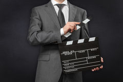Man wearing costume holding movie clapper board Royalty Free Stock Photo