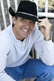 Man wearing cowboy hat. A friendly, smiling man wearing a cowboy hat holding brim royalty free stock photography