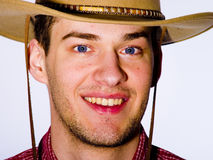 Man wearing cowboy hat. Portrait of smiling young man wearing cowboy hat, white background Stock Photo