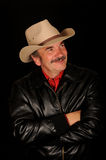 Man wearing cowboy hat. Rugged man with arms crossed wearing a cowboy hat and black leather jacket. Burt Reynolds celebrity look-a-like stock images