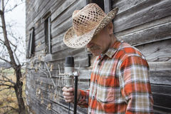 Man wearing cowboy hat holding a microphone. Royalty Free Stock Photo