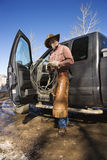 Man Wearing Cowboy Hat With Lariat and Truck. Cowboy standing with a lariat next to the open door of a pickup truck. Vertical shot Royalty Free Stock Photo