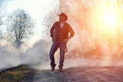 A man is wearing a cowboy hat and a loso in the field. American. Farmer in a field wearing a jeans hat and with a lasso in the smoke of a fire. A man walks stock photo