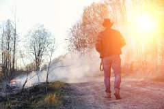 A man is wearing a cowboy hat and a loso in the field. American. Farmer in a field wearing a jeans hat and with a lasso in the smoke of a fire. A man walks royalty free stock photography