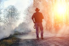 A man is wearing a cowboy hat and a loso in the field. American. Farmer in a field wearing a jeans hat and with a lasso in the smoke of a fire. A man walks royalty free stock images