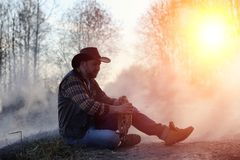 A man is wearing a cowboy hat and a loso in the field. American. Farmer in a field wearing a jeans hat and with a lasso in the smoke of a fire. A man walks royalty free stock photos