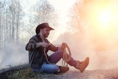 A man is wearing a cowboy hat and a loso in the field. American. Farmer in a field wearing a jeans hat and with a lasso in the smoke of a fire. A man walks stock image