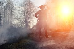 A man is wearing a cowboy hat and a loso in the field. American. Farmer in a field wearing a jeans hat and with a lasso in the smoke of a fire. A man walks stock photography