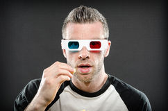 Man wearing 3d glasses eating popcorn. Image of a man wearing 3d glasses eating popcorn royalty free stock photography