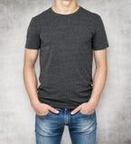 Man wearing dark grey t-shirt, concrete background. Stock Image