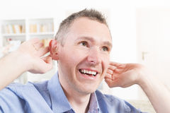 Man wearing deaf aid. In ear attempting to hear something stock image
