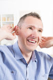 Man wearing deaf aid. In ear attempting to hear something stock photo