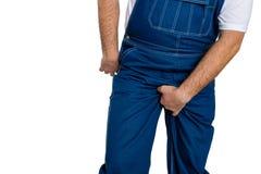 Man wearing denim dungarees scratching his crotch Stock Photo