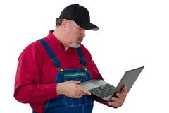 Man wearing dungarees holding laptop. Adult male worker wearing dungarees holding laptop while standing against white background royalty free stock photography