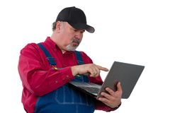 Man wearing dungarees standing with laptop. Adult male worker wearing dungarees using laptop while standing against white background royalty free stock image