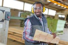 Man wearing earmuffs holding plank wood Stock Image