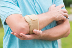 Man wearing elbow brace. To reduce pain royalty free stock photo