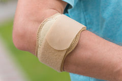 Man wearing elbow brace. To reduce pain royalty free stock image