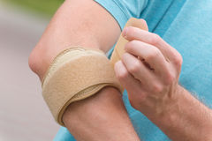 Man wearing elbow brace. To reduce pain stock photo