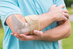 Man wearing elbow brace. To reduce pain stock photos