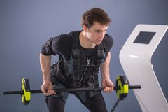 Man working out EMS training with barbell closeup, power pose. Man wearing EMS costume working out with barbell closeup, power pose Stock Photos