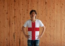 Man wearing England flag color shirt and standing with akimbo on the wooden wall background royalty free stock photo