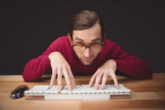 Man wearing eye glasses typing on computer keyboard Royalty Free Stock Photo