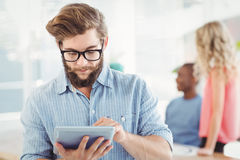 Man wearing eyeglasses using digital tablet at office Royalty Free Stock Photography