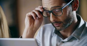 Man wearing eyeglasses using tablet.Corporate business team work office meeting.Three caucasian businessman and. Businesswoman people group talking strategy stock footage