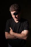 Man Wearing an Eyepatch. Young caucasian man on black background wearing an eyepatch royalty free stock photos