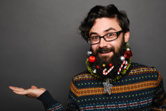 Man wearing eyewear showing something on the palm. Handsome man wearing eyewear showing something on the palm of her hand. Christmas decorated beard with toys Stock Photography