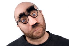 Man wearing fake nose. And glasses with mustashe and eyebrows over a white background stock photography