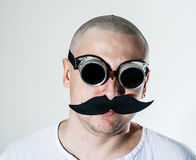 Man wearing false moustache and goggles. Portrait of a man wearing false moustache and black welding goggles stock photography