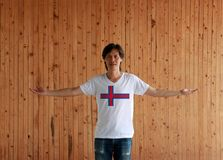 Man wearing Faroe Islands flag color shirt and standing with arms wide open on the wooden wall background royalty free stock photos