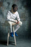 The man wearing fencing suit with sword against gray Stock Images