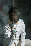 The man wearing fencing suit with sword against gray. The man wearing fencing suit posing with sword against gray studio background Royalty Free Stock Photos